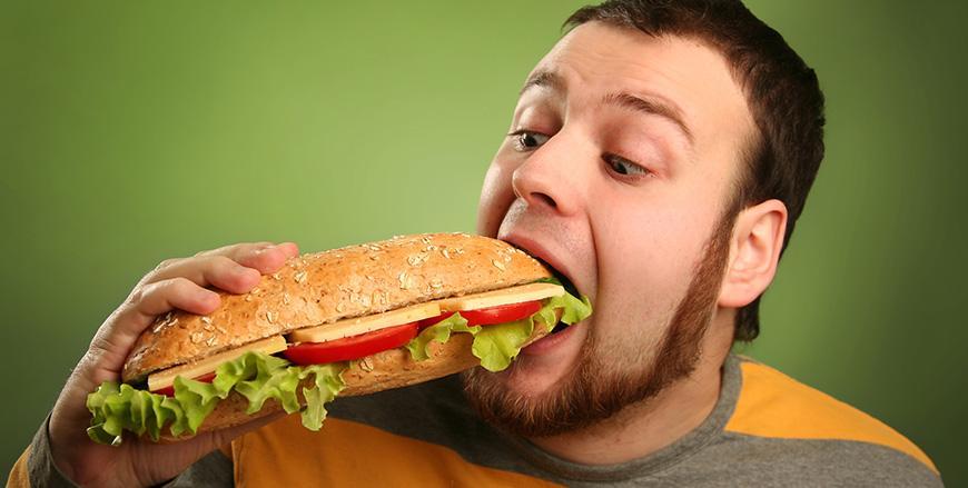 funny guy eating hamburger on green background