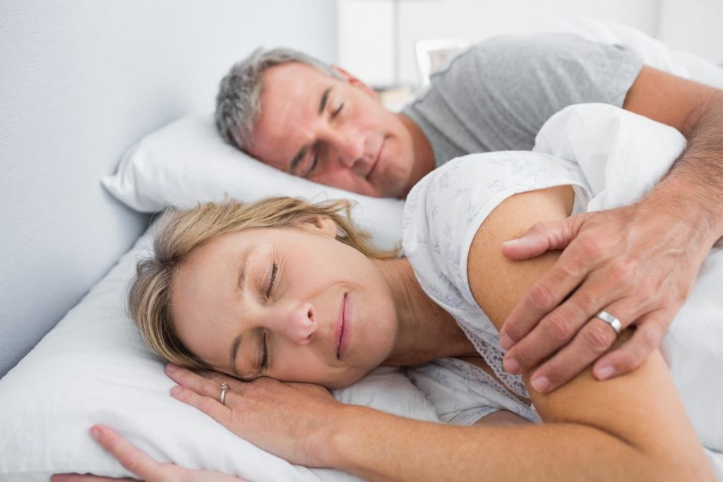 Couple sleeping and spooning in bed in bedroom at home