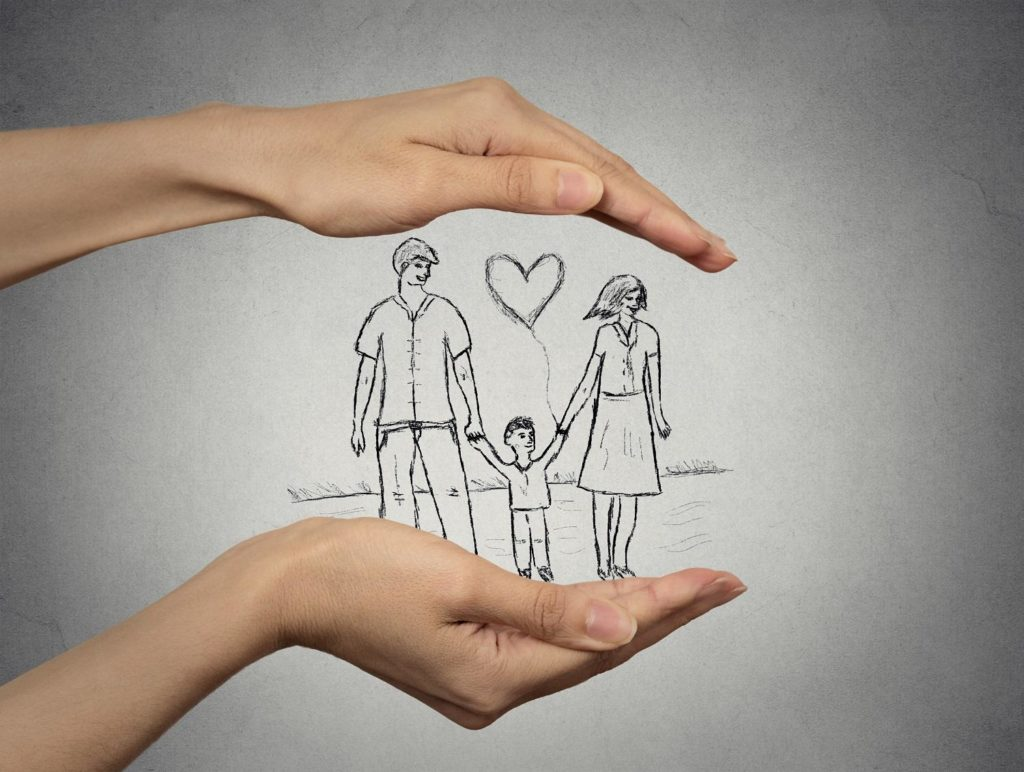 close up of woman's hands protecting happy family, mother, father, child. Family abstract in palms on grey wall background. Safe childhood, parenting. Love care compassion safety secure future concept